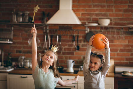 Girls in costume dancing playing in kitchen at home
