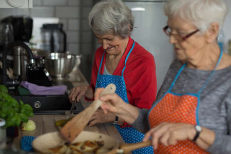 Senior friends cooking food together in kitchen at home LANG_EVOIMAGES