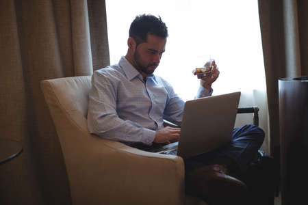 Businessman using laptop while having whisky in hotel room LANG_EVOIMAGES