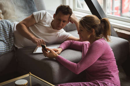 Couple using mobile phone in living room at home LANG_EVOIMAGES