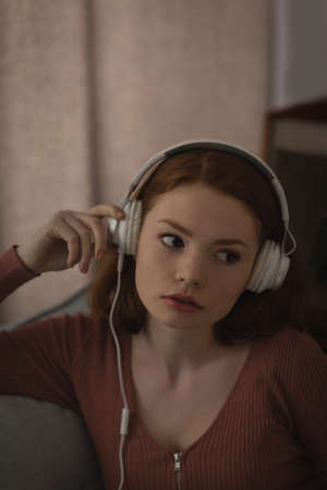 Woman listening music on headphones at home LANG_EVOIMAGES