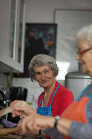 Senior friends interacting while cooking food in kitchen at home