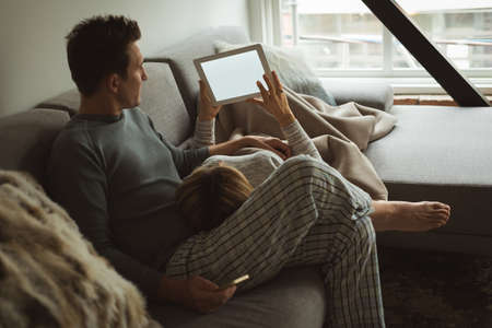 Couple using digital tablet in living room at home