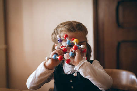 Girl looking through molecule model at home LANG_EVOIMAGES
