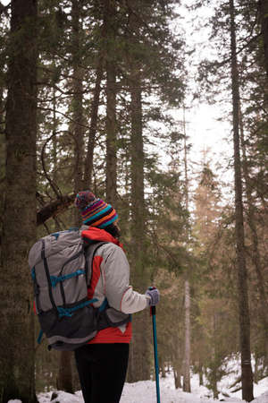 Thoughtful woman with backpack and hiking pole in forest LANG_EVOIMAGES