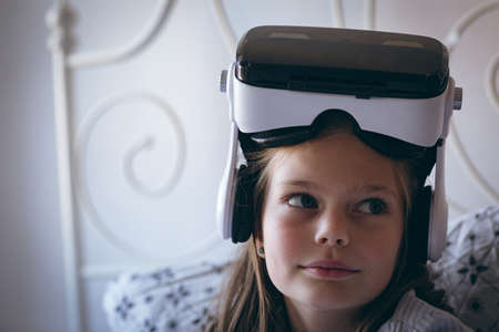 Girl with virtual reality headset sitting on bed at home