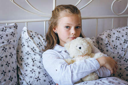 Portrait of girl playing holding teddy bear on bed