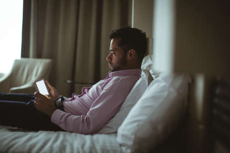 Businessman using digital tablet in hotel room