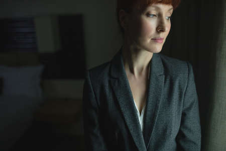 Thoughtful Businesswoman standing in hotel room LANG_EVOIMAGES