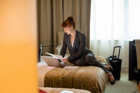 Businesswoman looking at documents on a bed in hotel room