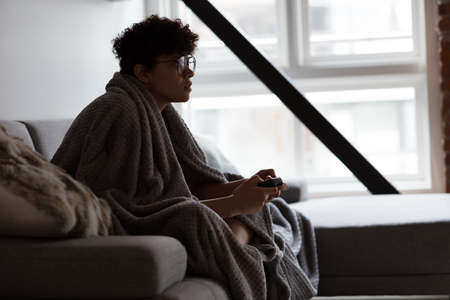 Beautiful woman playing video game while relaxing on sofa in living room