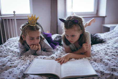 Sisters reading a book on bed in bedroom LANG_EVOIMAGES