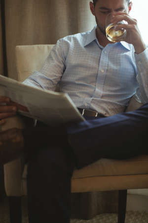 Businessman reading newspaper while having whisky in hotel room
