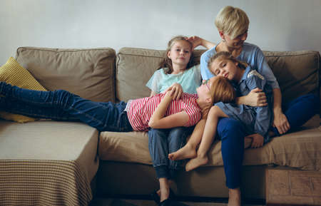 Mother and kids relaxing on sofa in living room LANG_EVOIMAGES