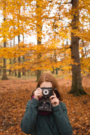 Woman taking photo with vintage camera in the park during autumn LANG_EVOIMAGES