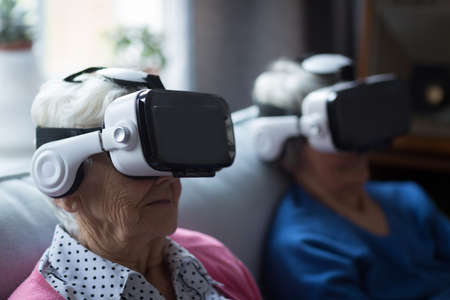 Senior friends using virtual reality headset at home LANG_EVOIMAGES