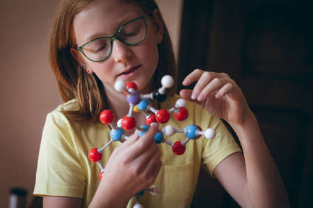 Attentive girl experimenting molecule at home