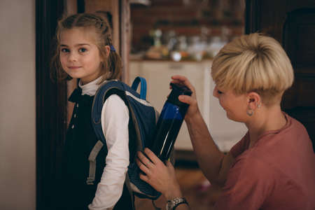 Mother keeping water bottle in daughter bag pack at home