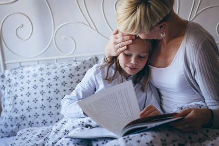 Affectionate mother kissing her daughter while reading book in bedroom