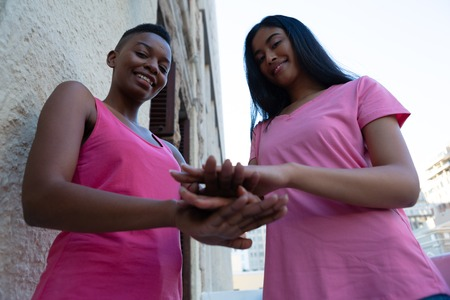 Friends joining hands for breast cancer awareness low angle view