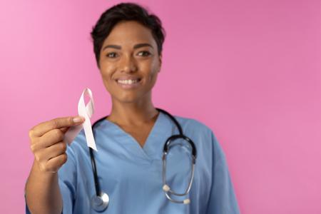 Smiling nurse holding breast cancer awareness pink ribbon
