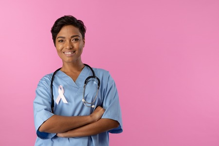 smiling nurse with crossed arms wearing pink ribbon om a pink background