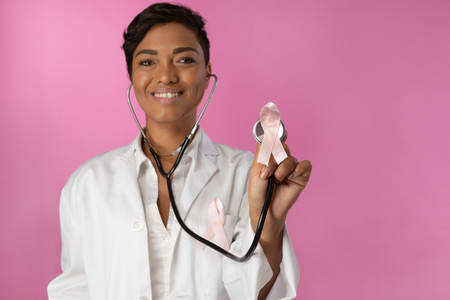 Smiling nurse wearing breast cancer awareness holding pink ribbon on a pink background