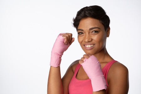 Smiling woman for breast cancer awareness on white background with hands up