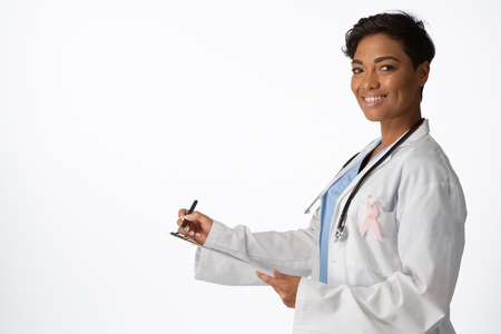 Smiling female doctor wearing breast cancer awareness pink ribbon writing on a note pad on a white background Stock Photo