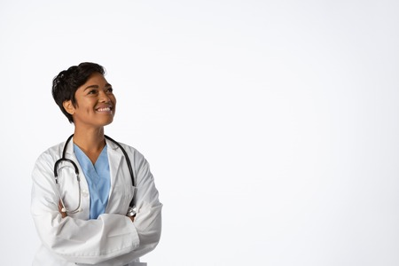 Smiling hopeful female doctor with crossed arms on a white background Stock Photo
