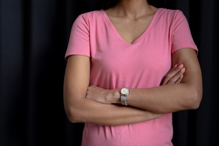 women in pink for breast cancer focus on crossed arms on a black background Stock Photo
