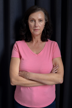 women in pink for cancer crosses their arms on a black background Stockfoto
