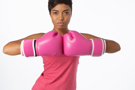 Standing woman for breast cancer awareness in boxing gloves on white background