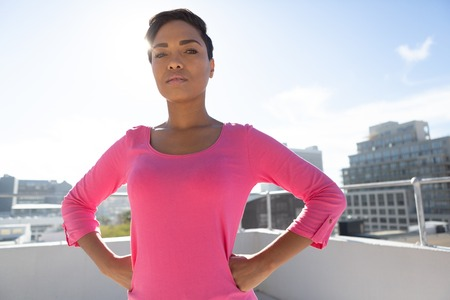 Serious looking woman standing confident for breast cancer awareness in pink shirt against urban background