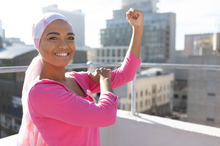 Strong woman wearing mantra scarf in the city with breast cancer awareness Stock Photo