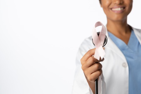 Breast cancer awareness pink ribbon on a stethoscope with a white background Stock Photo