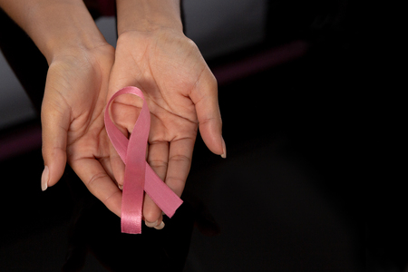Hands show pink ribbon in fight against breast cancer against black background