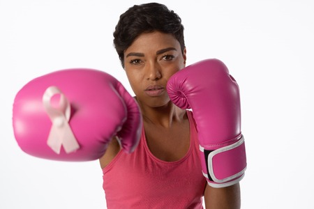 Woman in boxing gloves fighting for breast cancer awareness on white background Stock Photo