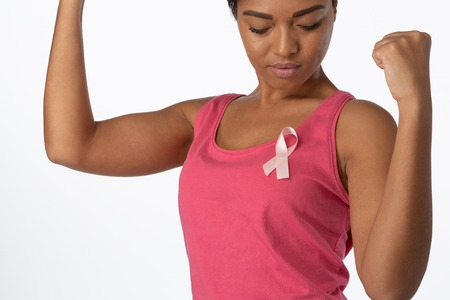 Woman putting up fists and looks at pink ribbon for breast cancer awareness