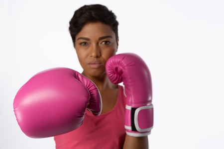Woman with boxing gloves for breast cancer awareness on white background