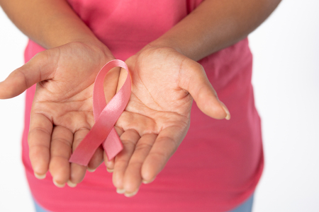 Woman hold ribbon in both hands for breast cancer awareness against white background
