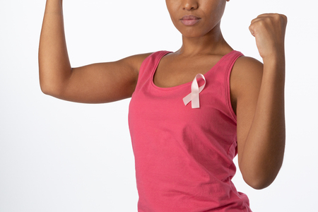 Woman putting up fists for breast cancer awareness with pink ribbon on white background Stock Photo