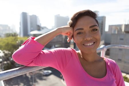 Smiling woman standing outside for breast cancer awareness against urban back ground Stock Photo