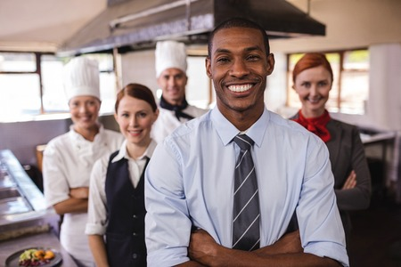 Group of hotel staffs standing with arms crossed in kitchen at hotel 写真素材