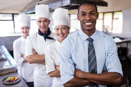 Grupo de chefs y gerente de pie con los brazos cruzados en la cocina del hotel