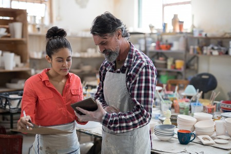 Male and female potter discussing over tablet pc in the pottery workshop 写真素材