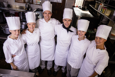 Group of chefs standing together in kitchen at hotel 写真素材