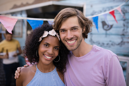 Portrait of happy couple standing near food truck