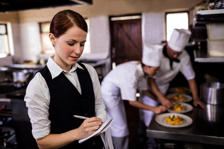 Female waitress noting an order on notepad in kitchen at hotel Imagens