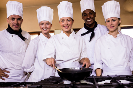 Female chef preparing food in kitchen at hotel